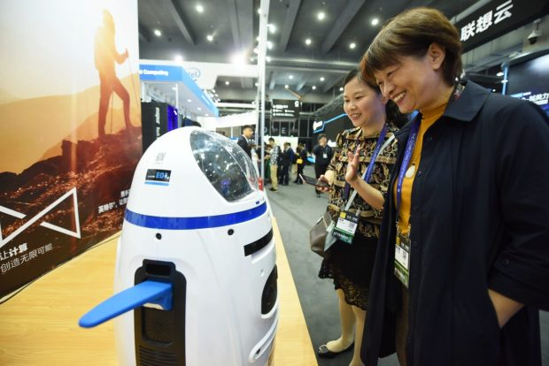"""Visitors interact with intelligent robots during """"The Computing Conference 2017"""" in Hangzhou, capital of east China's Zhejiang Province on October 11, 2017. (Photo by People's Daily Online)"""