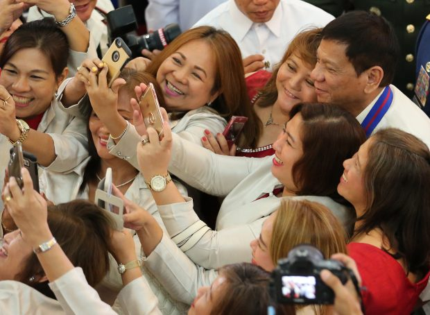 "Women guests take a selfie with Philippine President Rodrigo Duterte, right, after the ""Assumption of Command"" ceremonies of new Police Chief, Director General Ronald Dela Rosa at Camp Crame, Philippine National Police headquarters, in suburban Quezon city, Manila, Philippines on Friday, July 1, 2016. Duterte, who was sworn in as the Philippines' 16th president, has given himself a colossal campaign promise to fulfill, eradicating crime especially drug trafficking, smuggling, rapes and murder in three to six months. (Photo: AP)"