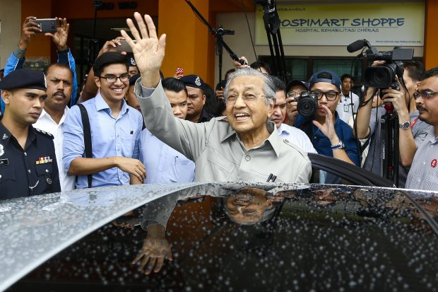 Former Malaysian Prime Minister Mahathir Mohamad, center, waves to the members of media after being denied to visit jailed former Deputy Prime Minister Anwar Ibrahim at the Cheras Rehabilitation Hospital in Kuala Lumpur, Malaysia, Wednesday, Jan. 10, 2018. Malaysia's opposition alliance has named 92-year-old former Prime Minister Mahathir Mohamad as its prime minister candidate for upcoming general elections to boost its chances of wrestling power from a coalition that has ruled since independence. (AP Photo/Sadiq Asyraf)