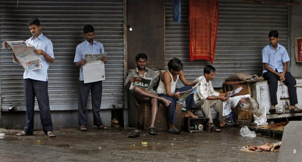 FILE- In this July 15, 2011 file photo, Indians read newspapers at Zaveri bazar, a market in Mumbai, India. India's Ministry of Information and Broadcasting has withdrawn a sweeping new order clamping down on journalists accused of spreading fake news. The U-turn on Tuesday came hours after the ministry announced that reporters' press credentials could be suspended simply for an accusation of spreading fake news. (AP Photo/Aijaz Rahi, File)