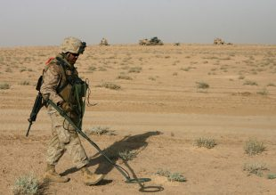 Lance Cpl. Enoch E. Chavarria, 21, a combat engineer with Route Clearance Platoon, Company A, 3rd Combat Engineer Battalion, Regimental Combat Team 5, walks with a mine detector Aug. 14 while searching for mines on the Iraq and Syrian border. The platoon marked two minefields and detonated six mines. Route Clearance Platoon's responsibilities normally include patrolling the roadways of Iraq to ensure the safe travel of Coalition forces. Though trained in explosives, this is the first time this deployment that the platoon has detonated any explosives they have found.