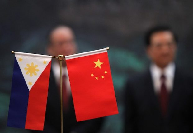 epa02889822 The Philippines' and China' national flags are seen as Philippine President Benigno Aquino III (L) and his Chinese counterpart Hu Jintao stand in the background during a signing ceremony in the Great Hall of the People in Beijing, China on 31 August 2011. Aquino is on a state visit to China to improve trade relations between the two countries.  EPA/HOW HWEE YOUNG