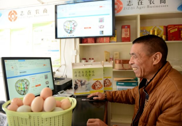 On November 19, 2018, in the e-commerce service station of Gulougou Village, Peng'an County, Sichuan Province, a staff is busy picking up agricultural and sideline products purchased from poor households, which would be sold through e-commerce channels after packaging. (Guo Anping Zhou Liang / People's daily online