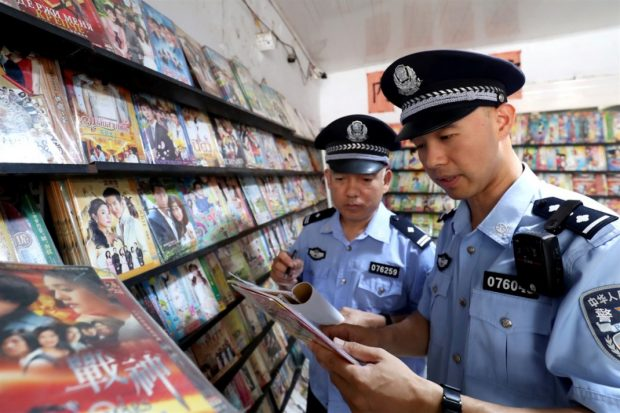 Lawenforcement officers in Xincai county, central China's Henan province conduct an inspection at a video store on Aug.23, 2018. (Photo by Wang Yuxin from People's Daily Online)