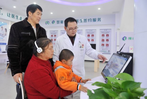 Photo taken on March 4, 2019 shows a staff worker from Dingnan county's smart medical comprehensive service center in east China's Jiangxi province instructs citizens to conduct medical treatment through its internet remote consultation