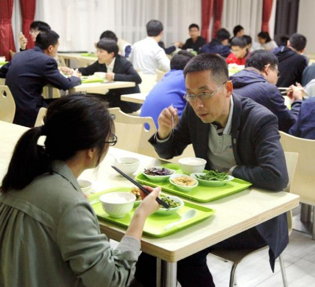Shi Yigong talks with a student at lunchtime. Photo by Zhao Yongxin from People's Daily