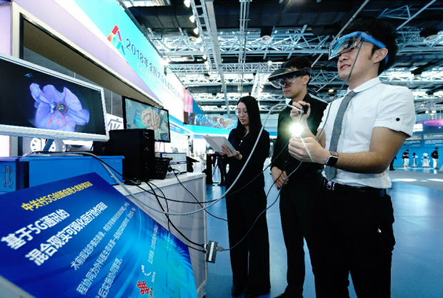 Visitors experience the 5G-enabled VR medical visualization platform during the 2018 National Mass Innovation and Entrepreneurship Week in Beijing, October 8, 2018. The equipment was provided by a Beijing-based company, which enables users to operate a tele-mentored live surgery over  5G connection. (Photo by He Yong from People's Daily)