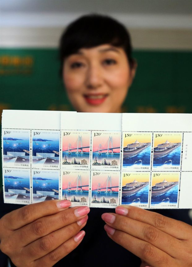 """An employee of a postal office in Boxing county, Binzhou city, Shandong province is showing a set of special stamps on the theme of """"Hong Kong-Zhuhai-Macao Bridge"""". The stamps were co-issued by China Post, Hongkong Post and the Macao Post and Telecommunications Bureau to commemorate the opening of the bridge on October 30, 2018. (Photo: Chen Bin from People's Daily Online)"""