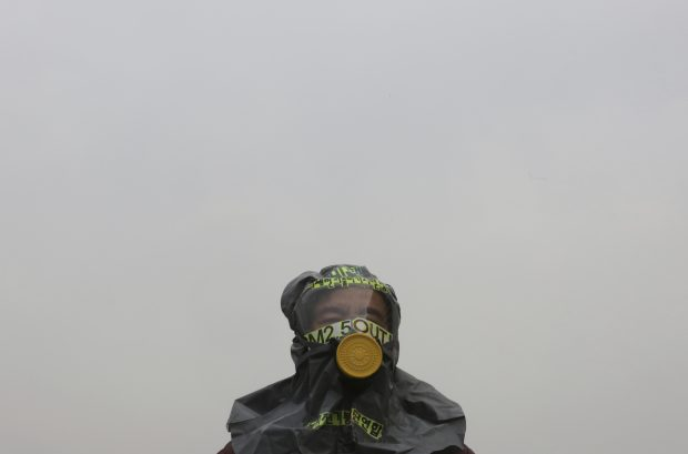 """A South Korean environmental activist wearing a gas mask stands in protest demanding the government to ease air pollution in Seoul, South Korea, Friday, March 15, 2019. South Korean President Moon Jae-in on March 6, proposed a joint project with China to use artificial rain to clean the air in Seoul, where an acute increase in pollution has caused alarm. The signs read: """"The fine dust particles."""" (AP Photo/Ahn Young-joon)"""