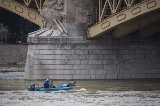 epa07631228 Members of the rescue team lift a buoy into their motorboat on River Danube next to Margaret Bridge, the scene of a boat accident, in Budapest, Hungary, 06 June 2019. A sightseeing boat carrying 33 South Korean tourists was crashed by a large river cruise ship and sank in River Danube at a pier of Margaret Bridge on May 29, killing at least fifteen tourists. Seven tourists were injured, 11 persons, including the two crew members, went missing.  EPA/Marton Monus   HUNGARY OUT