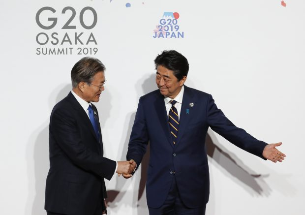 South Korean President Moon Jae-in, left, is welcomed by Japanese Prime Minister Shinzo Abe upon his arrival for an welcome and family photo session at G-20 leaders summit in Osaka, Japan, June 28, 2019. (Kim Kyung-Hoon/Pool Photo via AP)