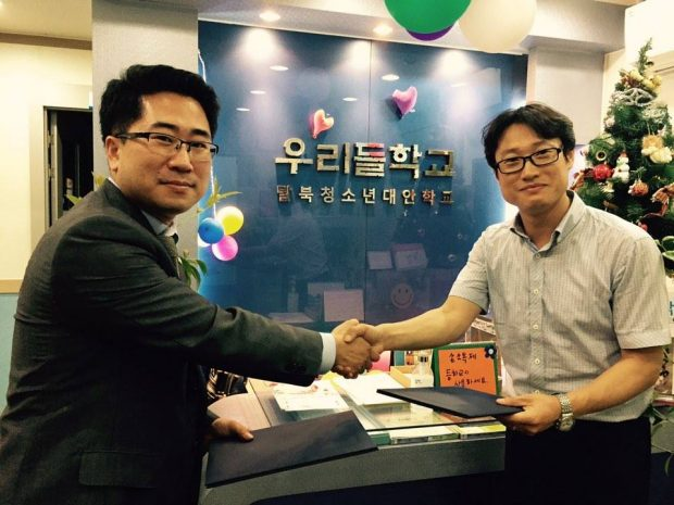 After signing a MOU with Wooridul school on July 1, 2019, Mr. Park(L) takes a picture with Mr. Yun, the president at Wooridul school, one of the schools in which North Korean students attend.