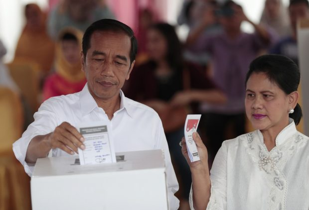 "Indonesian President Joko ""Jokowi"" Widodo and his wife Iriana cast their ballots during the election at a polling station in Jakarta, Indonesia, Wednesday, April 17, 2019. Tens of millions of Indonesians were voting in presidential and legislative elections Wednesday after a campaign that pitted the moderate incumbent against an ultranationalist former general whose fear-based rhetoric warned the country would fall apart without his strongman leadership. (AP Photo/Dita Alangkara)/2019-04-17 15:17:42/"