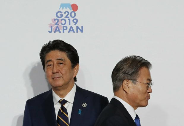 South Korean President Moon Jae-in, right, is welcomed by Japanese Prime Minister Shinzo Abe upon his arrival for a welcome and family photo session at G-20 leaders summit in Osaka, western Japan, Friday, June 28, 2019. (Kim Kyung-Hoon/Pool Photo via AP)