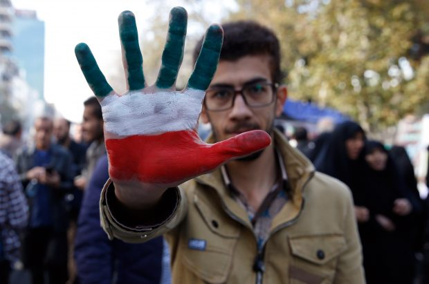 epa07140547 An Iranian man shows his hand painted with Iran's national flag colors during an anti-US demonstration marking the 39th anniversary of US Embassy takeover, in front of the former US embassy in Tehran, Iran, 04 November 2018. Media reported that thousands of protesters chanting 'Death to America' gathered at the former US embassy in Tehran to mark the 39th anniversary of the start of the Iran hostage crisis. Iranian students occupied the embassy on November 04, 1979 after the USA granted permission to the late Iranian Shah to be hospitalized in the States. Over 50 US diplomats and guards were held hostage by students for 444 days. US President Donald J. Trump's administration announced on 02 November 2018, that it will reimpose sanctions against Iran that had been waived under the 2015 Iran nuclear deal (the Joint Comprehensive Plan of Action, JCPOA). The US sanctions will take effect on 05 November 2018, covering Iran's shipping, financial and energy sectors. In 2015, five nations, including the United States, worked out a deal with the Middle Eastern country that withdrew the sanctions, one of former US President Barack Obama's biggest diplomatic achievements.  EPA/ABEDIN TAHERKENAREH/2018-11-04 19:23:01/