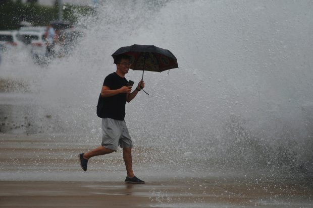 Holidaymakers watch huge waves from a tidal bore caused by Typhoon Danas, the 5th typhoon of the year, surging past a barrier on the banks along the seacoast in Qingdao city, east China's Shandong province, 18 July 2019.
