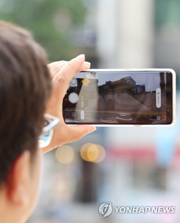A Seoul citizen looks at an image of Donuimun, one of the four main old gates in Seoul, with his smartphone in front of Donuimun Museum Village in central Seoul on Aug. 20, 2019, as the gate is restored digitally with augmented reality (AR) technology. (Yonhap)
