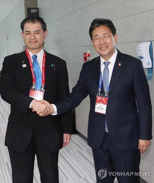 Park Yang-woo (R) and Masahiko Shibayama shake hands before the start of their bilateral meeting in Incheon on Aug. 29, 2019 (Yonhap)