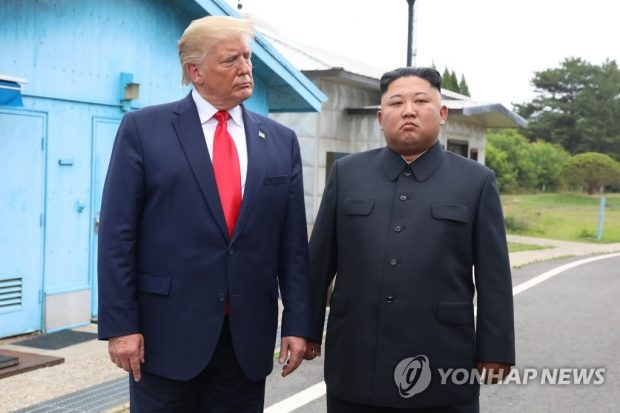 U.S. President Donald Trump (L) stands with North Korean leader Kim Jong-un before they hold talks at the Freedom House on the southern side of the truce village of Panmunjom in the Demilitarized Zone, which separates the two Koreas, on June 30, 2019. (Yonhap)