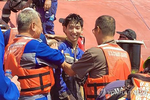 This image released by the U.S. Coast Guard via AP shows a crew member of the cargo ship Golden Ray as he is helped off the capsized ship (Yonhap)