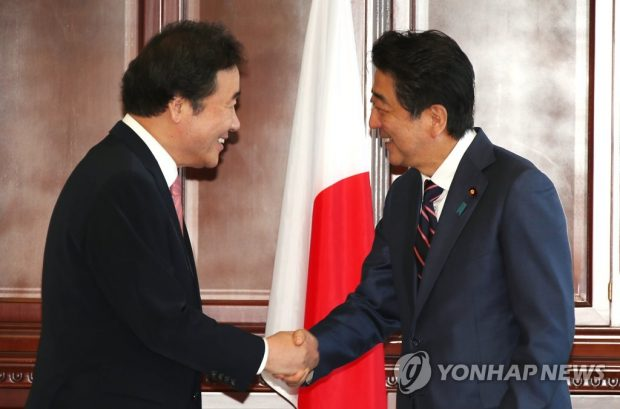This photo, taken on Sept. 11, 2018, shows South Korean Prime Minister Lee Nak-yon (L) shaking hands with Japanese Prime Minister Shinzo Abe. (Yonhap)