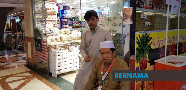 Ahmad Ansyar (left) communicates in Kelantanese Malay with his Malaysian customers. (Bernama)