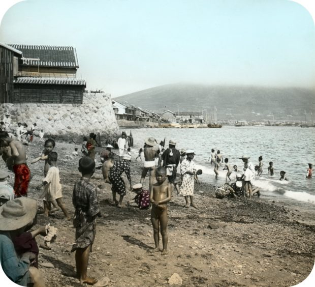This photo, provided by the Seoul Museum of History, shows children sunbathing on a beach in the southern port city of Busan. (Yonhap)