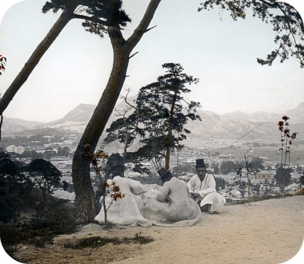 This photo, provided by the Seoul Museum of History, shows three men sitting under a pine tree on Mount Nam in Seoul. (Yonhap)
