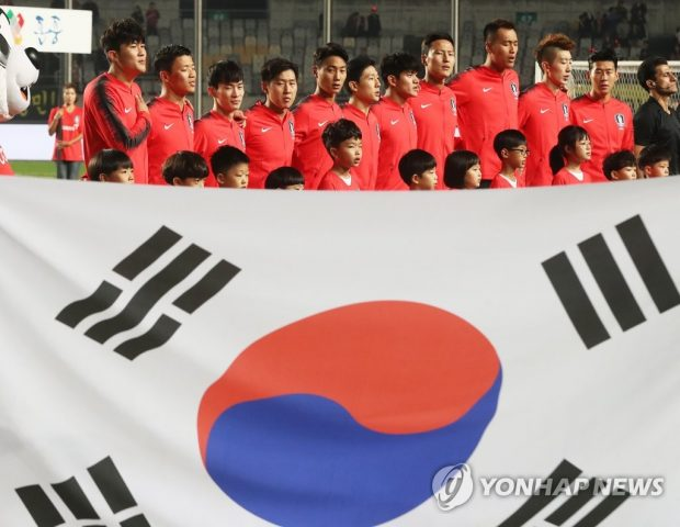 The starting members of the South Korean men's national football team stand for their national anthem (Yonhap)