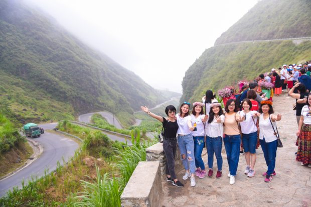 Tourists pose for a photo at the Tham Ma mountain slope by the Happiness Road in Dong Van District