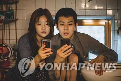 """This film still shot, provided by CJ Entertainment, shows the protagonists of Director Bong Joon-ho's """"Parasite"""" trying to search for a free Wi-Fi network at their basement home. (Yonhap)"""