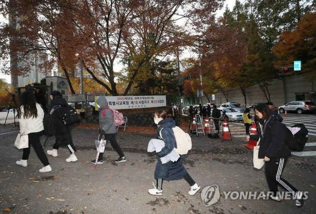 Students bundled up against the cold enter Seoul Banpo High School to take the national college entrance exam on Nov. 14, 2019. (Yonhap)