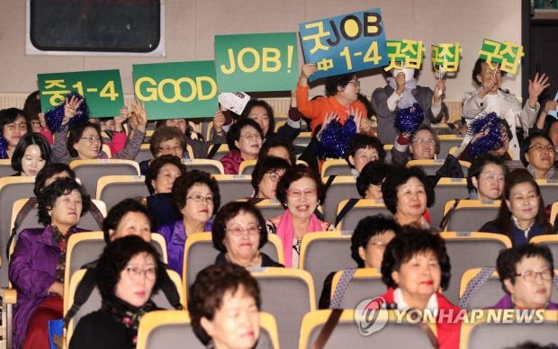 """Students hold up signs saying """"Good Job"""" as they cheer for their classmates taking part in the English Speech Contest (Yonhap)"""