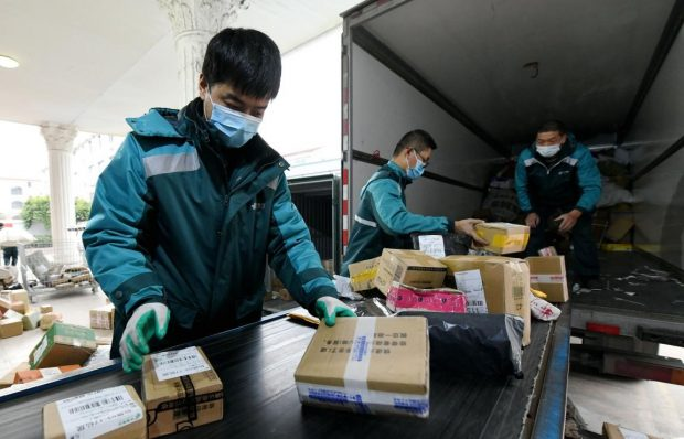 Couriers sort packages at a handling station of a branch office of China Post in Xianju county, east China's Zhejiang Province, Feb. 10, 2020. Photo by Wang Huabin, People's Daily Online