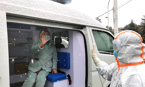 """A cured COVID-19 patient waves goodbye to a medical worker at the """"Wuhan Livingroom"""" makeshift hospital in Wuhan, central China's Hubei Province, Feb. 15, 2020. (Photo: Xinhua)"""