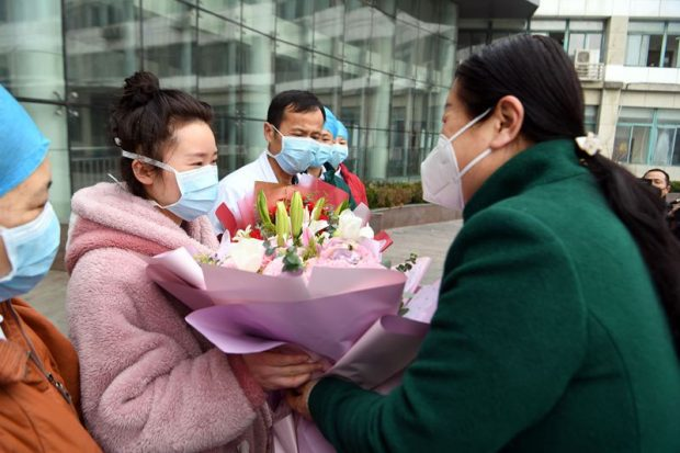 A 25-year-old woman surnamed Li, accompanied by medics, walks out of the isolation ward of People's Hospital of Bozhou, east China's Anhui Province at 9:00 am, Jan. 29, 2020. She is the first cured patient of the novel coronavirus in Bozhou and among the first batch in Anhui. (Photo by Zhang Yanlin from People's Daily Online)