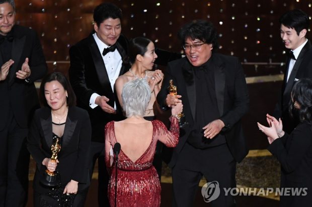 "In this photo released by AFP, ""Parasite"" producers Kwak Sin-ae (L) and Bong Joon-ho (R) accept the best picture award for the film. (Yonhap)"