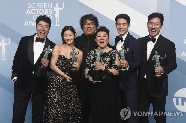 """This photo, moved by the Associated Press, shows director Bong Joon-ho (3rd from L) and actors of """"Parasite"""" posing after winning the award for outstanding performance by a cast in a motion picture at the Screen Actors Guild Awards held in Los Angeles on Jan. 19, 2020. (Yonhap)"""