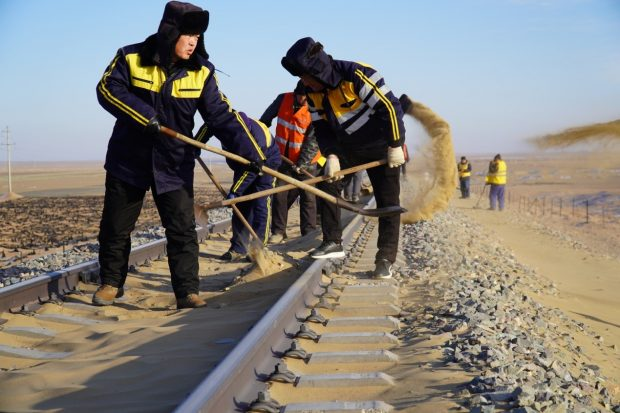 Desertification control staff clear sand off the tracks on the Linhai–Ceke railway in Alashan League, north China's Inner Mongolia Autonomous Region, Jan.15, 2020. Tang Zhe/People's Daily Online