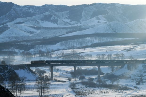 Photo taken on Jan. 17, 2020 shows a train runs on a railway line linking Jining district of Ulanqab and Tongliao, north China's Inner Mongolia Autonomous Region. The scene resembles an ink wash painting. Tang Zhe/People's Daily Online