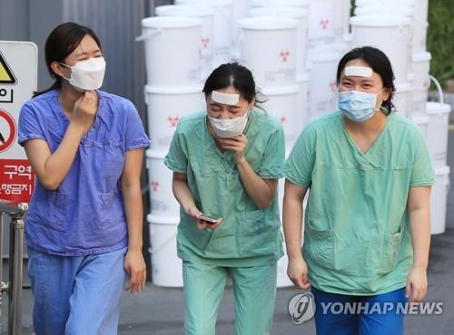 Medical staffers walk to a staff lounge after finishing a shift at Dongsan Hospital in coronavirus-hit Daegu, 302 kilometers southeast of Seoul, on March 24, 2020. (Yonhap)