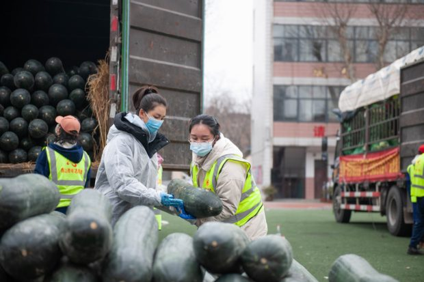 Hua Yuchen, a music teacher in Wuhan, takes on different assignments as a volunteer, including unloading donated supplies and taking the temperatures of drivers at a highway checkpoint. (China Daily)