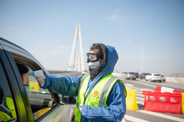 Hua Yuchen, a music teacher in Wuhan, takes on different assignments as a volunteer, including unloading donated supplies and taking the temperatures of drivers at a highway checkpoint. (Photo provided to China Daily])