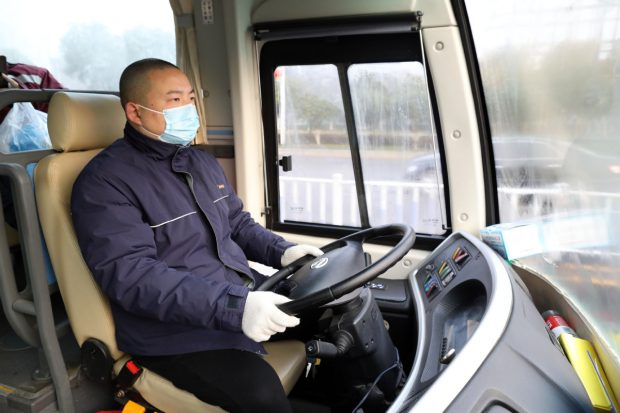 Wang Mian, a bus driver in the city, transports medical workers between the airport, residential buildings, hotels and hospitals. (Photo by Zhu Xingxin/China Daily)