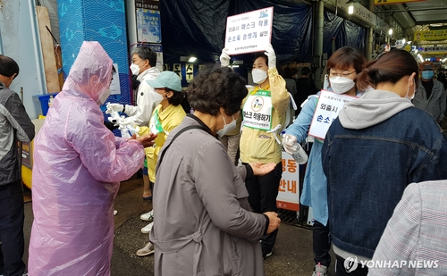 This photo provided by the city of Tongyeong shows local officials and volunteers holding a hand sanitation campaign at a market in the southwestern coastal city on May 3, 2020. (Yonhap)