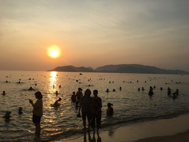 People swim at a beach in Nha Trang City on an early morning in late May