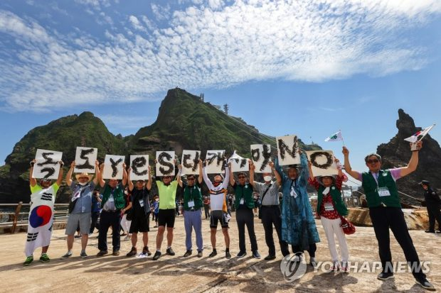 Visitors taking a group picture in Dokdo (Yonhap)