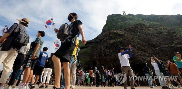 Visitors take photos on South Korea's easternmost islets of Dokdo amid the new coronavirus outbreak on Aug. 16, 2020. (Yonhap)