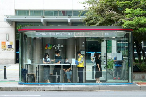"""Commuters on Aug. 3 wait for buses at a """"smart shelter"""" high-tech bus stop in Seongdong-gu District, Seoul. (Seongdong-gu District)"""