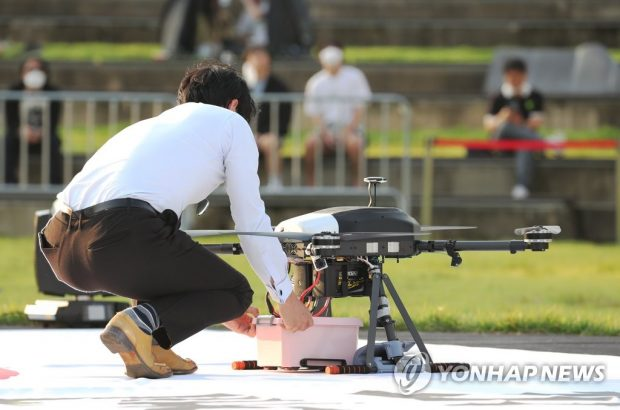 An individual receiving a food box delivery from a drone during a government-led test event in Sejong, 130 kilometers southeast of Seoul. (Yonhap)